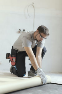 Man peeling back carpet wearing safety goggles